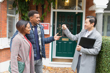 Real Estate Agent Giving House Keys To Couple Outside House For Sale