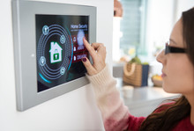 Woman Setting Touch Screen Home Alarm System