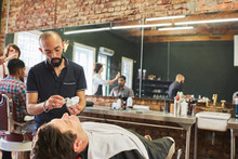 Male Barber Preparing To Shave Face Of Customer In Barbershop