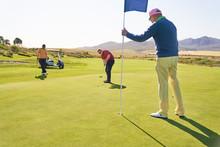 Men On Sunny Golf Putting Green