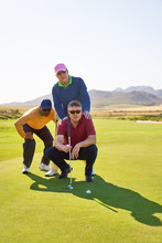 Male Golfers Planning Putt Shot On Sunny Golf Course Putting Green