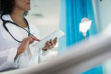 Female Doctor Using Digital Tablet In Hospital Room