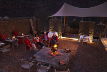 Senior Friends Relaxing With Wine At Fire Pit On Hotel Patio