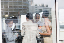 Smiling Business People Talking At Sunny Office Window