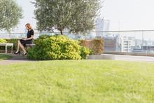 Businesswoman Working On Urban Rooftop Garden