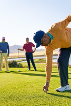 Male Golfer Preparing To Tee Off At Sunny Golf Tee Box