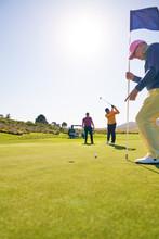 Male Golfer Putting Toward Hol...