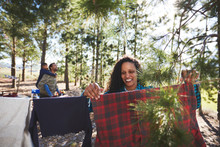 Smiling Woman Hanging Clothing...