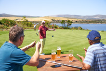 Happy Male Golfers Drinking Beer And Practicing Putting At Golf Course