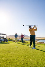 Male Golfer Teeing Off At Sunny Golf Course Tee Box