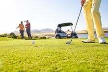 Golfer Preparing To Tee Off At Sunny Tee Box