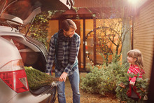 Father And Daughter Unloading Christmas Tree From Car Outside House