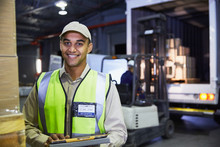 Portrait Smiling Worker In Front Of Forklift And Truck At Distribution Warehouse Loading Dock