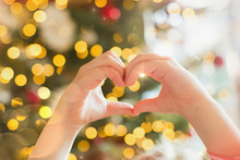 Close Up Hands Of Girl Forming Heart-shape In Front Of Christmas Tree