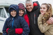 Portrait Affectionate Happy Family In Warm Clothing Outside Motor Home
