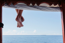 Bare Feet Hanging From Dock Ov...