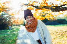 Portrait Happy Young Woman In Stocking Cap And Scarf In Sunny Autumn Park