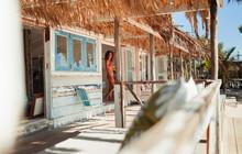 Woman In Bikini Standing In Doorway Of Sunny Beach Hut