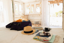 Suitcase, Sun Hat, Sunglasses, Book And Digital Tablet On Beach House Bed