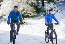 Couple Mountain Biking In Snowy Woods
