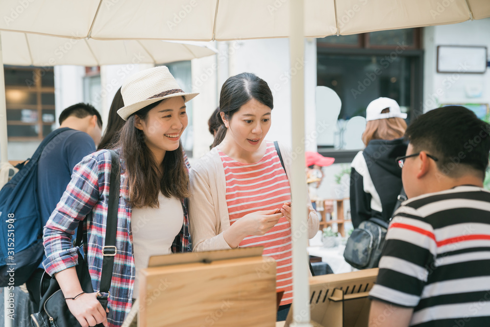 Fototapeta group of young female tourists at weekly creative market.  Best friends sharing free time on weekend having fun and shopping in old town tokyo japan. smiling girl guests looking at vendor seller.