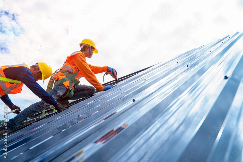 Fototapeta Portrait of technician is installing new roofs under construction.