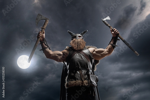 Photo Medieval warrior berserk Viking with tattoo with axes attacks enemy