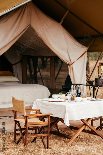 Luxury Safari tent camp with picnic table in Serengeti Savanna forest - Glamping Wallpaper Mural