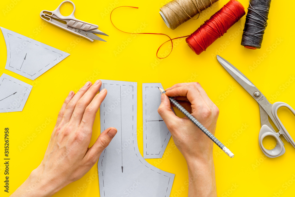 Fototapeta Tailor working. Women hands drawing patterns for clothes on yellow background top-down