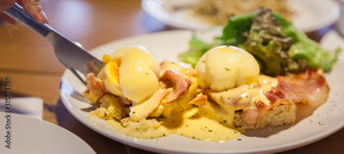 Photo Selective Focused Eggs Benedict, sandwich consists of 2 halves of English muffin topped with poached egg, bacon or ham and hollandaise sauce