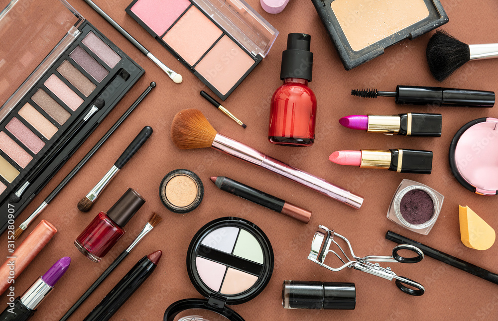 Fototapeta Make up cosmetics products against brown color background