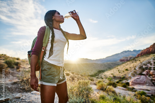 Fotomural african american woman taking a break to drink from water bottle while hiking at