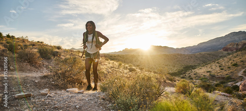 Obraz woman hiking at Red Rock Canyon during sunset with backpack - fototapety do salonu