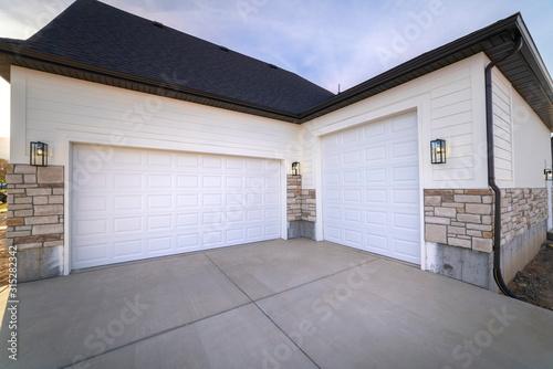 Fototapeta Two garage doors sharing a paved forecourt obraz
