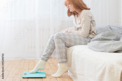 Photo teenager girl sitting on bed and scale on floor