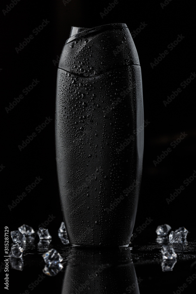 Fototapeta black sweaty plastic bottle for shampoo or shower gel on a black isolated background. there are also ice cubes in the background