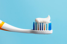 Toothbrush With White Toothpaste Close-up On Blue Background