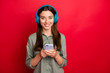 Leinwanddruck Bild - Photo of youngster lady using modern technology headphones listen popular song choosing telephone next audio track wear casual grey green shirt isolated red color background
