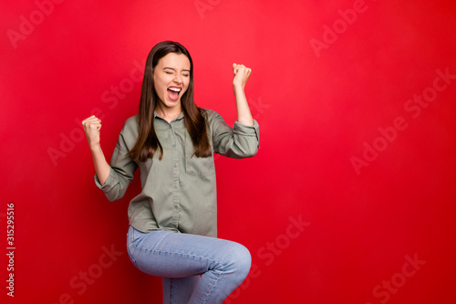 Fototapeta Photo of attractive funny lady yelling loud raising fists celebrating glory money lottery winning wear casual grey green shirt jeans isolated red color background obraz