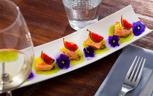 Ceviche from pickled red fish and cumquat a circle of kiwi, with figs at plate Canvas Print