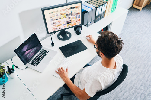 Obraz Overhead view of photographer sitting in office editing and managing portfolio - fototapety do salonu