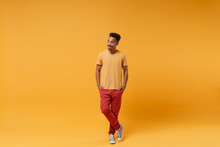 Smiling Young African American Guy In Casual Clothes Posing Isolated On Yellow Orange Wall Background, Studio Portrait. People Sincere Emotions Lifestyle Concept. Mock Up Copy Space. Looking Aside.