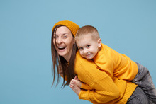 Woman In Yellow Clothes Have Fun Posing With Cute Child Baby Boy 4-5 Years Old. Mommy Little Kid Son Isolated On Blue Background Studio Portrait. Mother's Day Love Family Parenthood Childhood Concept.