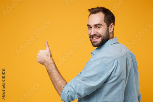 Obraz Back rear view of smiling young bearded man in casual blue shirt posing isolated on yellow orange background in studio. People lifestyle concept. Mock up copy space. Looking back, showing thumb up. - fototapety do salonu