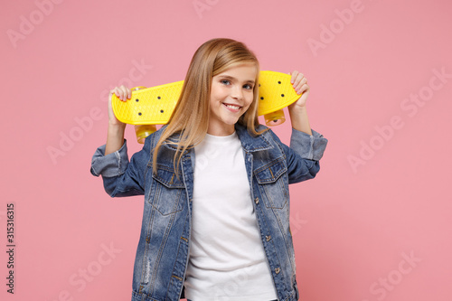 Obraz Smiling little blonde kid girl 12-13 years old in denim jacket posing isolated on pastel pink background children portrait. Childhood lifestyle concept. Mock up copy space. Hold yellow skateboard. - fototapety do salonu