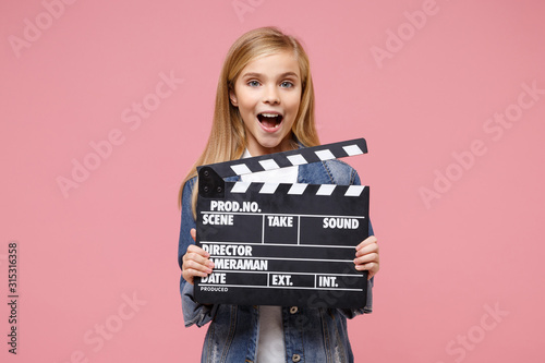 Fotografija Excited little blonde kid girl 12-13 years old in denim jacket posing isolated on pastel pink background