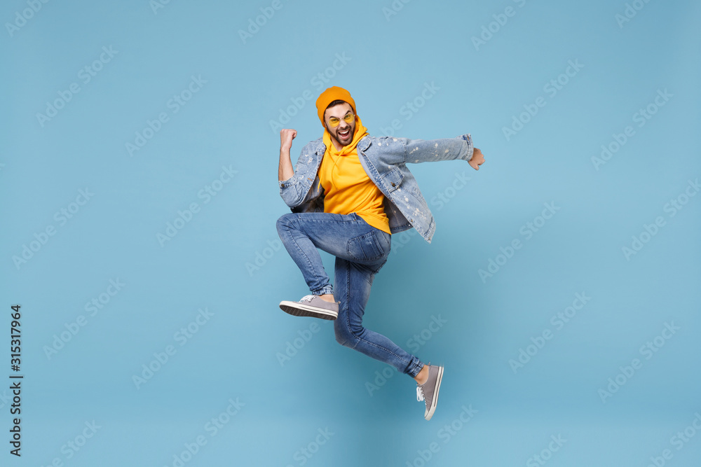 Fototapeta Side view of happy young hipster guy in fashion jeans denim clothes posing isolated on pastel blue background studio portrait. People lifestyle concept. Mock up copy space. Jump doing winner gesture.