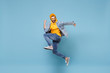 Side view of happy young hipster guy in fashion jeans denim clothes posing isolated on pastel blue background studio portrait. People lifestyle concept. Mock up copy space. Jump doing winner gesture.