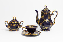 Closeup Of A Beautiful Cobalt Blue Colored Vintage Porcelain Tea Set With Golden Floral Pattern On White Background. The Set Includes A Tea Pot, A Sugar Bowl And A Tea Cup.