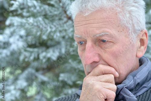 Obraz na plátně Portrait of sad senior man standing outdoors in winter